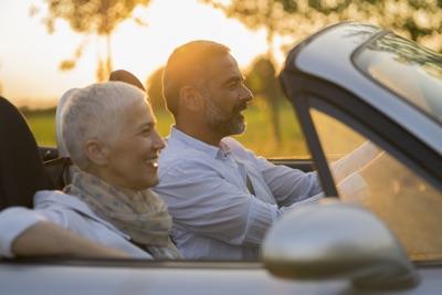 Paar mittleren Alters fährt im offenen Cabrio.
