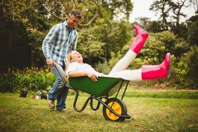 Paar mittleren Alters bei der Gartenarbeit. Sie sitzt lachend in der Schubkarre, die er schiebt.