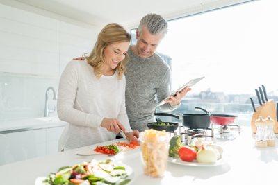 Paar mittleren Alters in einer modernen Küche beim Kochen. Sie schneidet das Gemüse, er hält das Kochbuch und schaut ihr lachend zu.