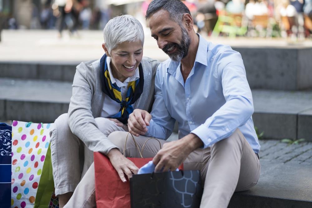Paar mittleren Alters beim Shoppen schaut gemeinsam in die Einkaufstaschen und lächeln dabei.