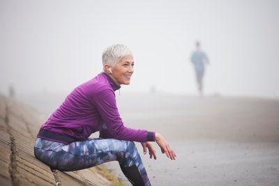 Frau mittleren Alters in Sportkleidung sitzt auf einer Deichmauer. Im nebeligen Hintergrund ist ein Jogger erkennbar.