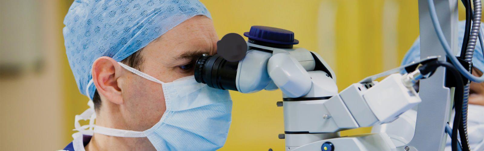 Augenchirurg blickt durch ein Operationsmikroskop.