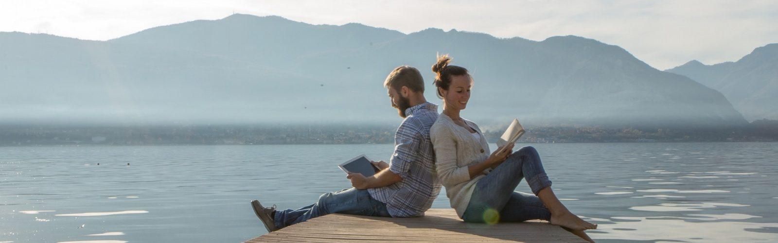 Mann und Frau sitzen Rücken an Rücken auf einem Steg am See und lesen. Hinter ihnen ist eine Bergkette zu sehen.