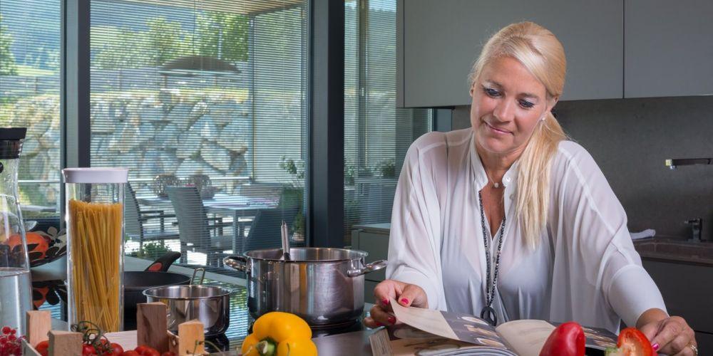 Attraktive Frau mittleren Alters schaut in ihrer modernen Küche beim Kochen in ein Kochbuch.