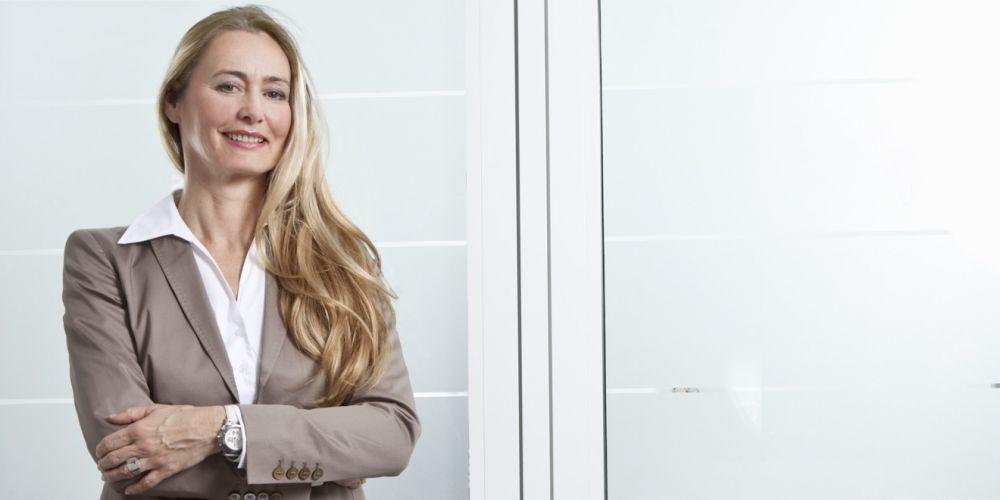 Attraktive Businessfrau um die 50 im Büro mit verschränkten Armen.