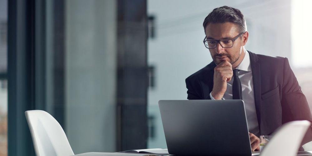 Mann im Büro, der mit Brille vor einem Laptop sitzt.