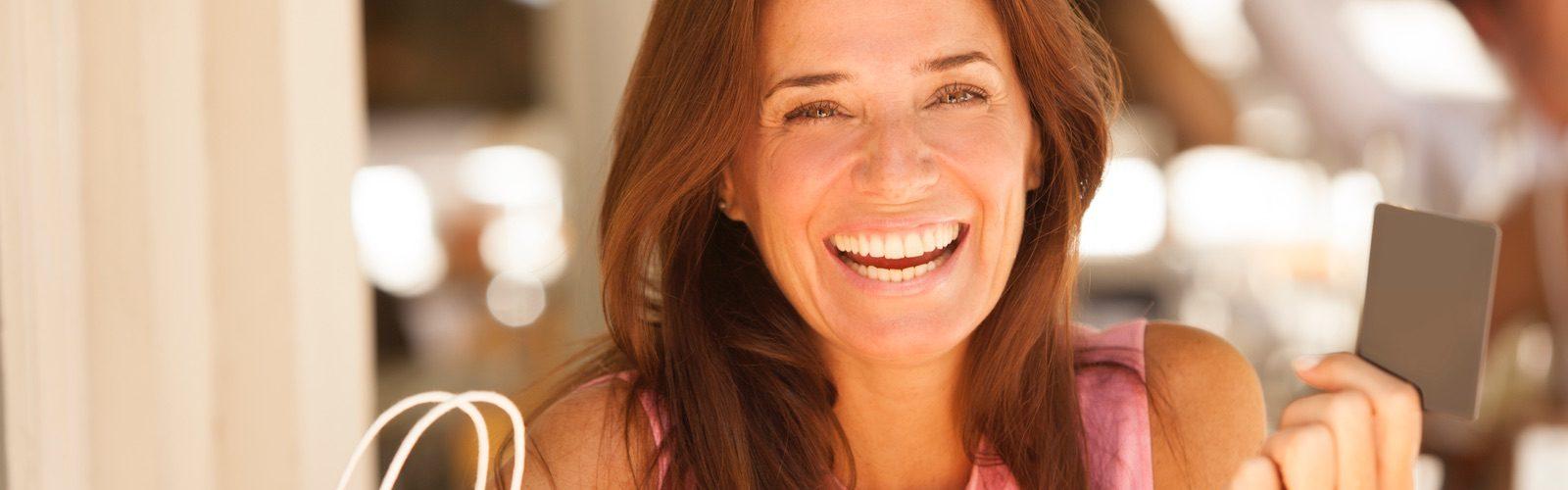 Attraktive Frau mittleren Alters schaut lächelnd in die Kamera und hält ihre Kreditkarte hoch.
