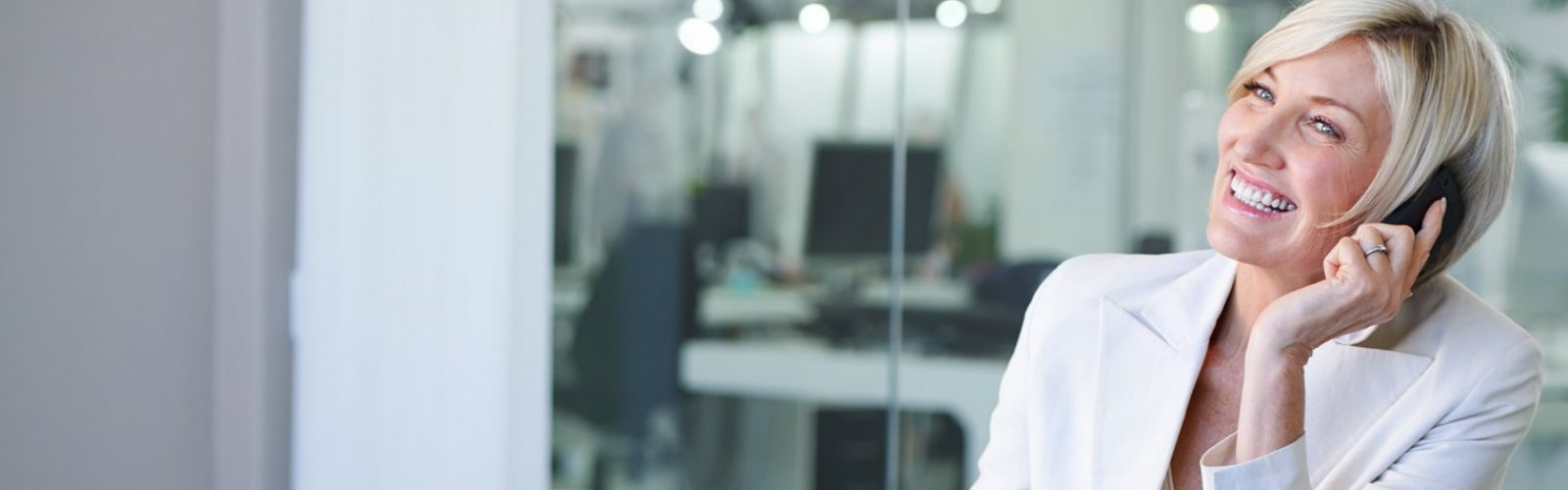 Frau mittleren Alters sitzt im Büro und telefoniert lächelnd.