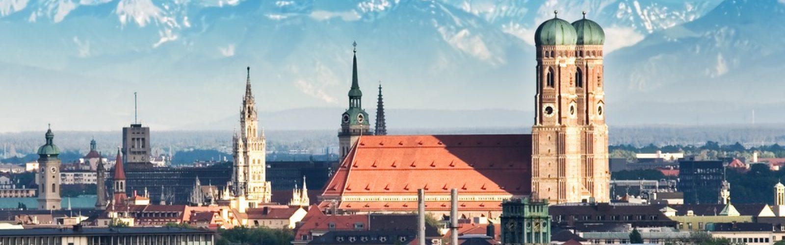 Foto von der Skyline aus München, im Hintergrund die Alpen.