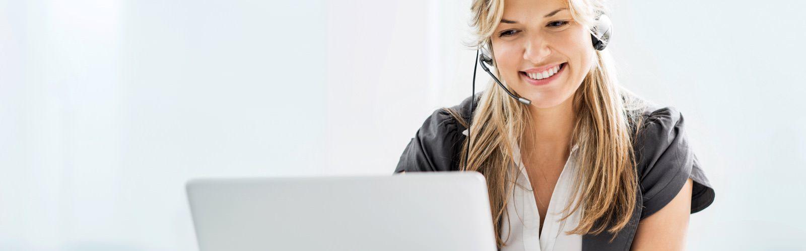 Telefonistin mit Headset sitzt an einem Computer.