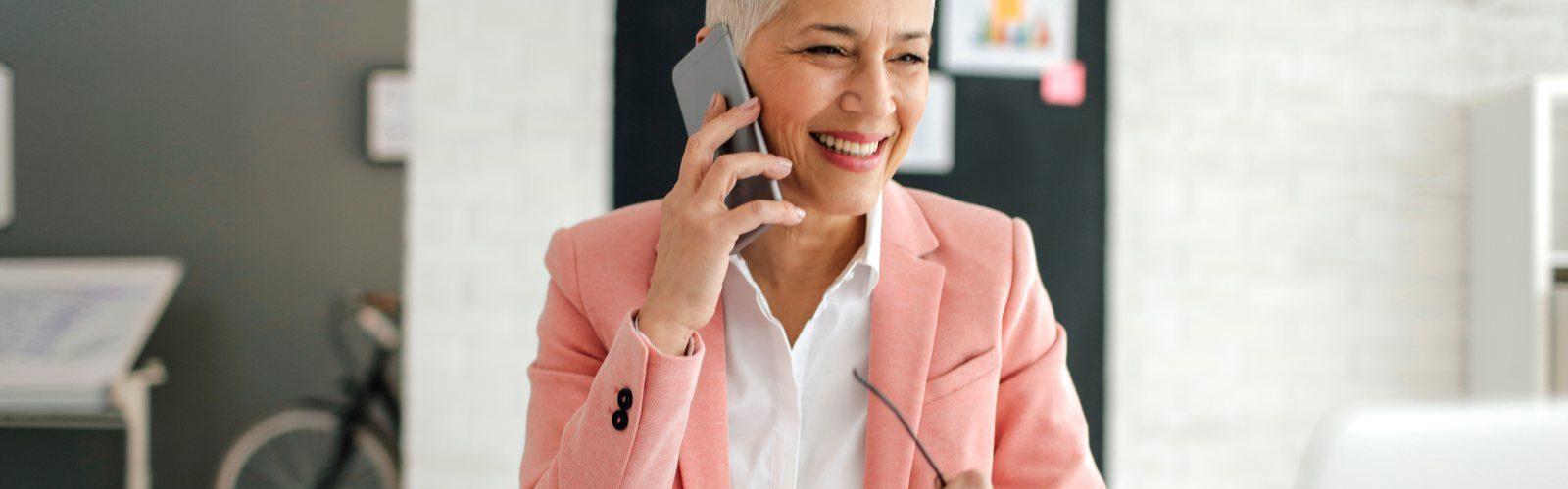 Eine Frau mittleren Alters sitzt im Büro und telefoniert mit einem iPhone. Im unscharfen Hintergrund erkennt man ein Loft-Büro.