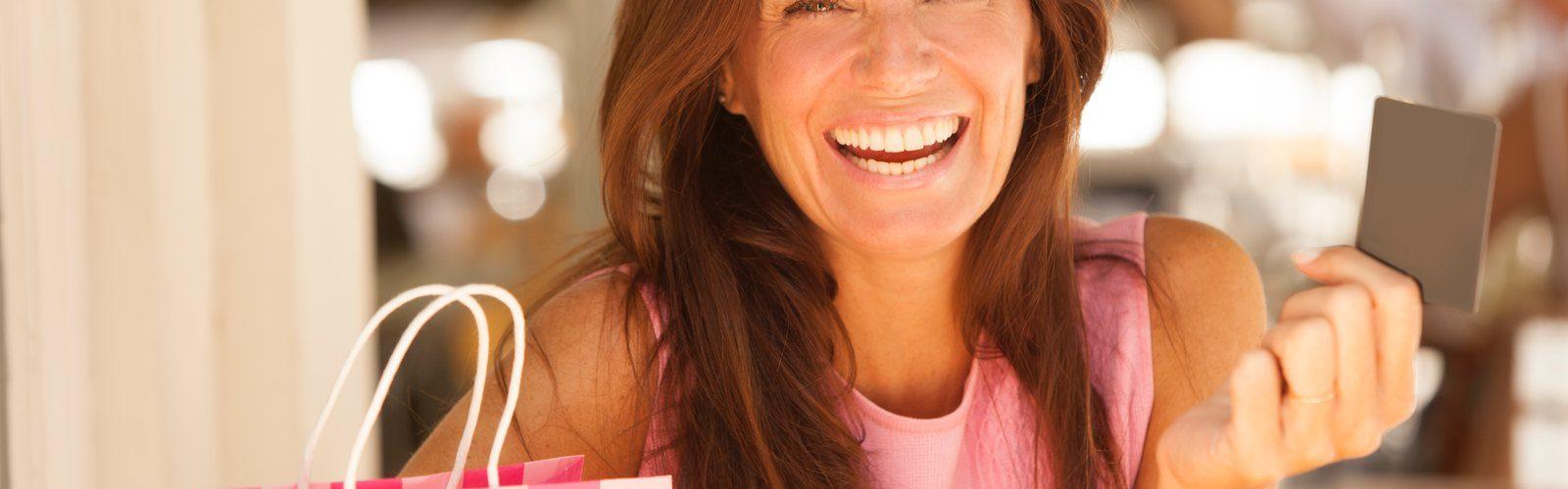 Eine dunkelhaarige Frau im rosa Kleid mit Einkaufstüte und Kreditkarte in der Hand schaut in die Kamera.
