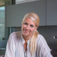 Blonde Frau in einer Küche schaut in die Kamera