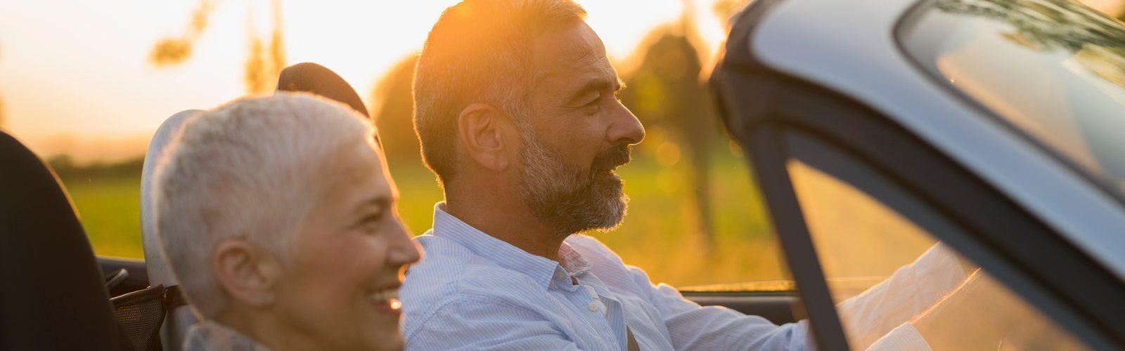 Pärchen mittleren Alters sitzt in einem offenen Cabrio und fährt in den Sonnenuntergang.