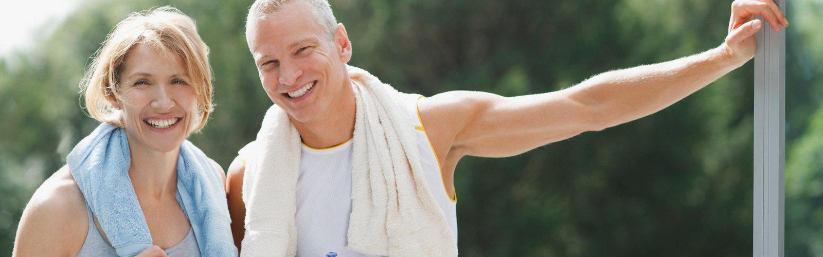 Pärchen mittleren Alters nach dem Sport. Beide haben ein Handtuch um den Hals und halten Trinkflaschen in den Händen.