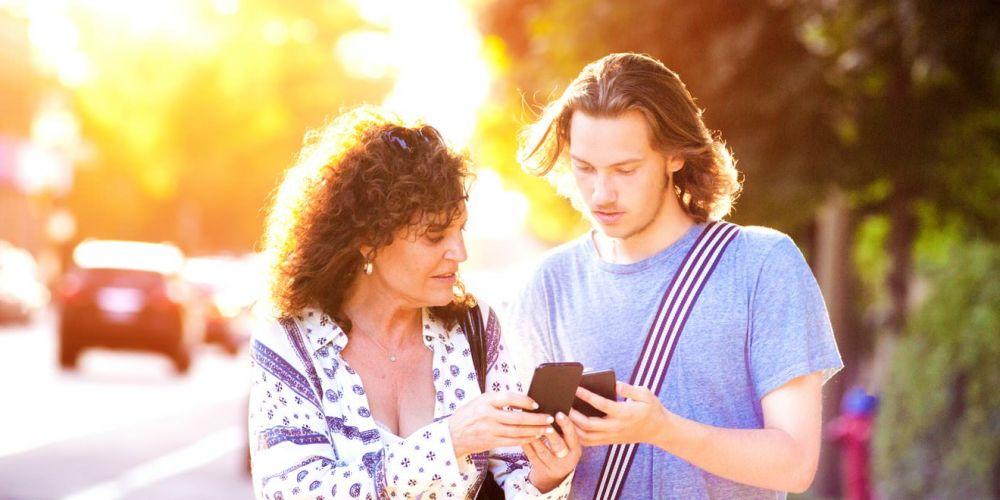 Mutter und Sohen gehen an einer Straße entlang. Der Sohn erklärt der Mutter etwas am Handy.