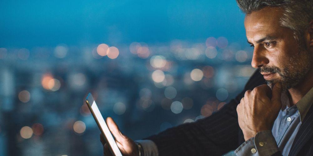 Mann mittleren Alters schaut in ein Tablet. Hinter ihm sind die Lichter der Stadt zu erkennen.