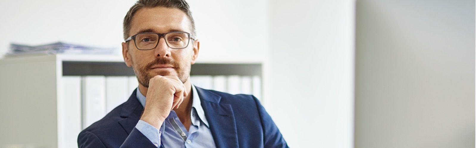 Mann über 45 mit Brille im Büro.